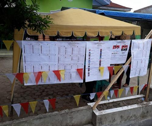 The staggeringly long list of candidates voters were choosing between hangs outside a polling station in North Sumatra. Photo from Wikimedia Commons/ Davidelit.